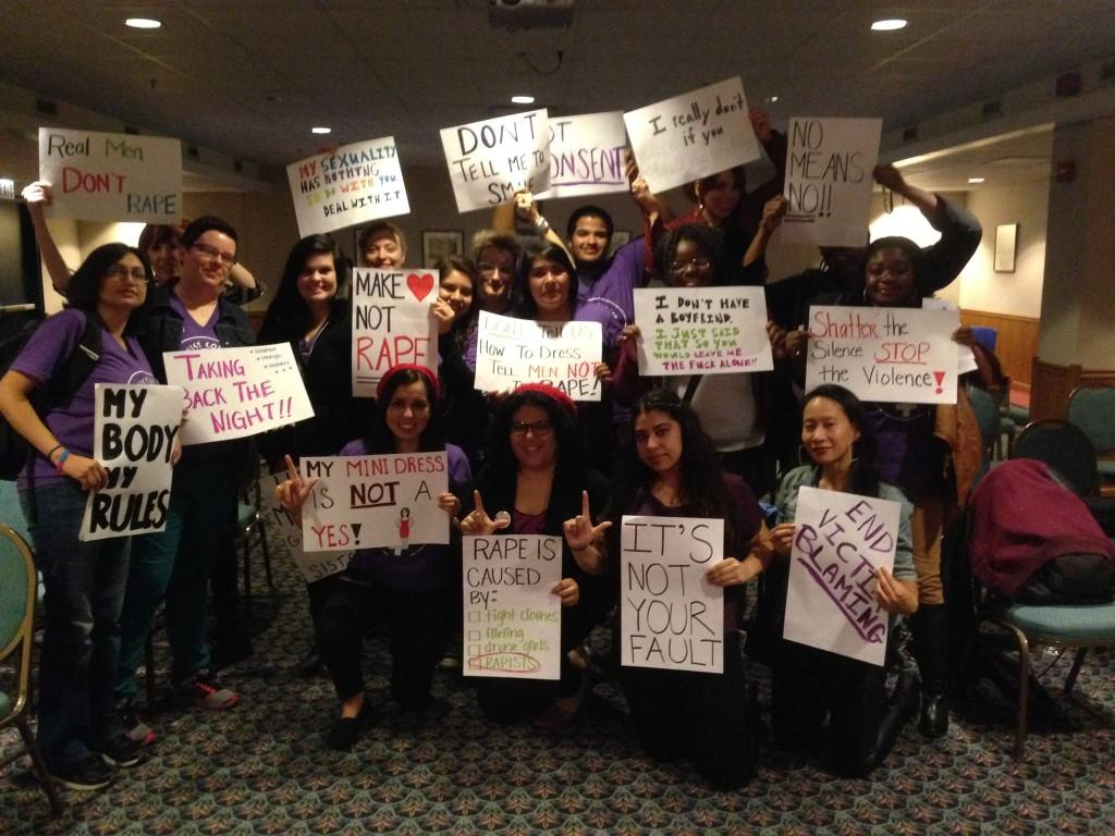 """Members of Feminist Collective and event attendees gathered at """"Take Back The Night"""" event at NEIU."""