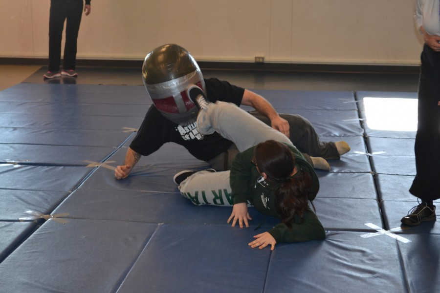A+student+demonstrates+self-defense+techniques+against+a+big-headed%2C+heavily+padded+opponent.