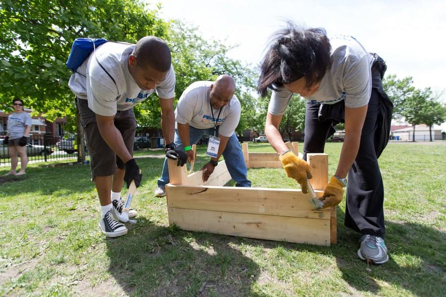 Volunteers at Chicago Cares' 2014 Serve-a-thon build a park bench, one of many diverse projects volunteers engage in during the annual day of service.