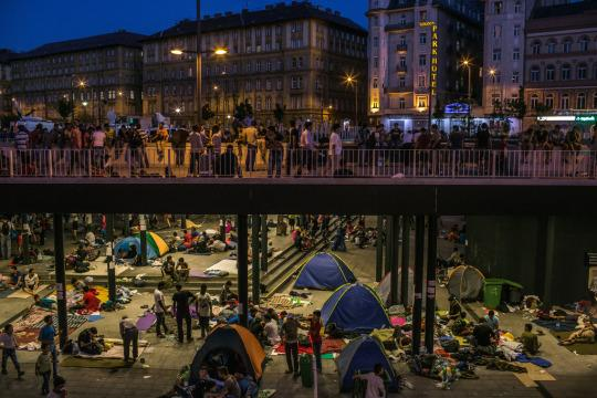 Refugee families set up camp underneath a Budapest bridge.