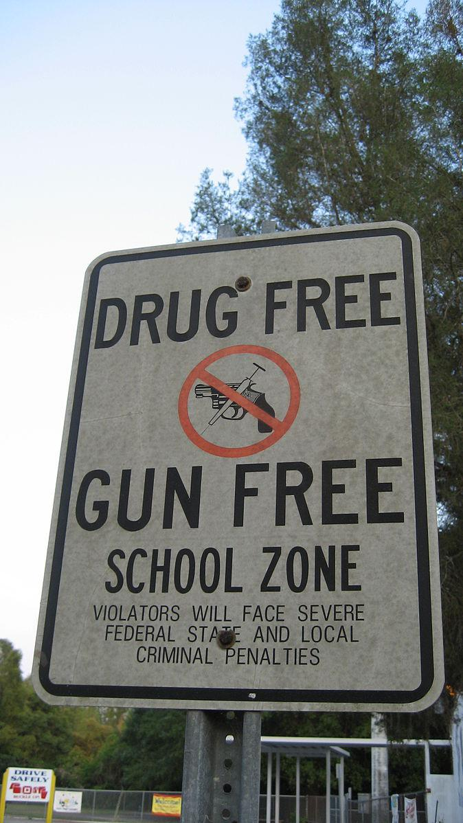 A drug free and gun free sign posted near a school zone.