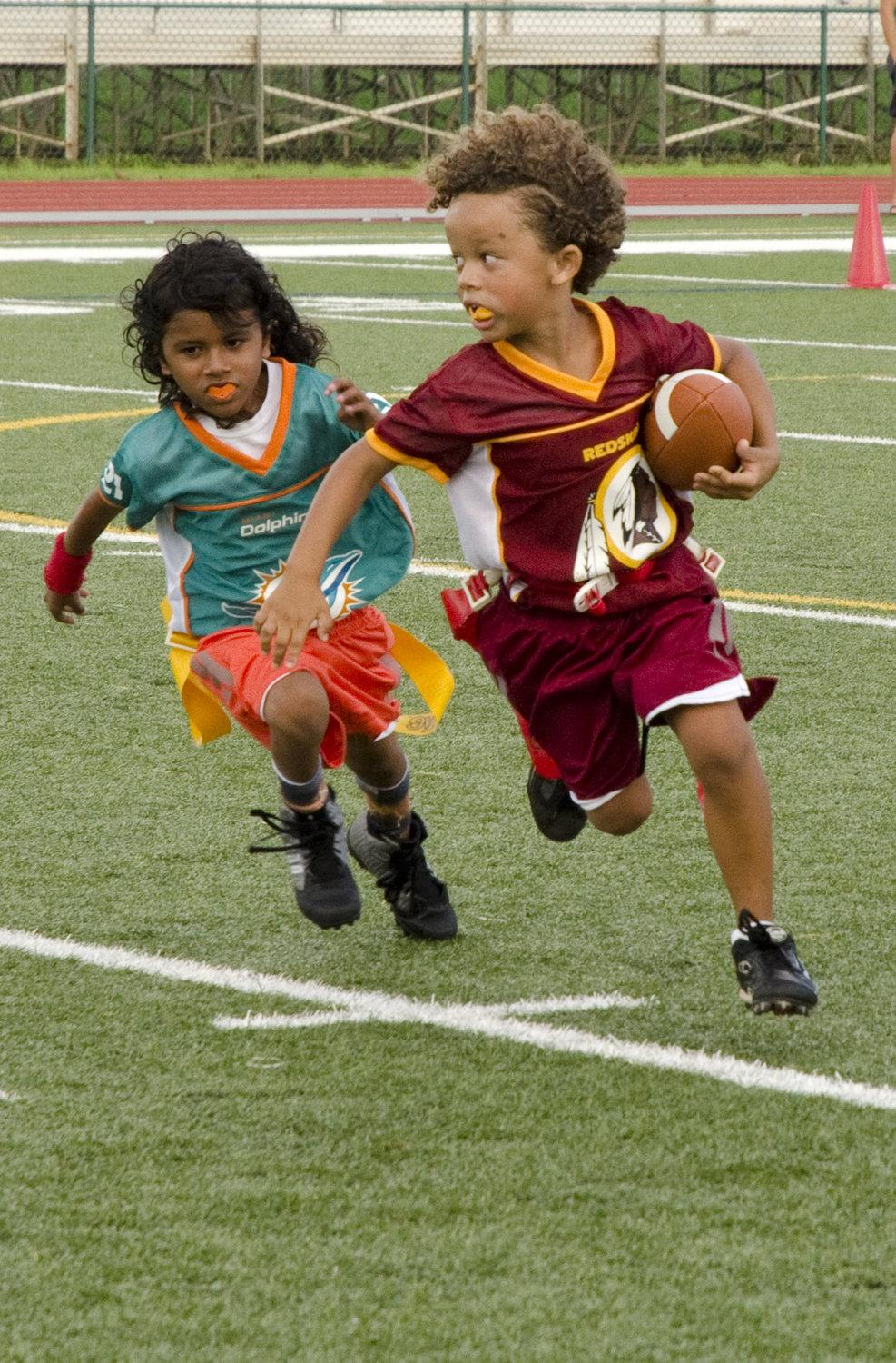 Mini Mite Miami Dolphins player Isaias Gonzalez II (left) pursues Mini Mite Washington Redskins player Malachai Cabrellis during a youth flag football game at Pop Warner Field, Oct. 25, 2014. The Redskins defeated the Dolphins. The youth flag football season runs through November. (U.S. Marine Corps photo by Kristen Wong)