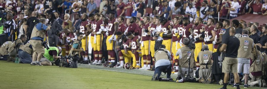 To+protest+police+brutality+and+racism%2C+some+Washington+Redskins+teammates+kneel+during+the+national+anthem+before+playing+against+the+Oakland+Raiders+on+Sept.+24.%0A%0A%0A
