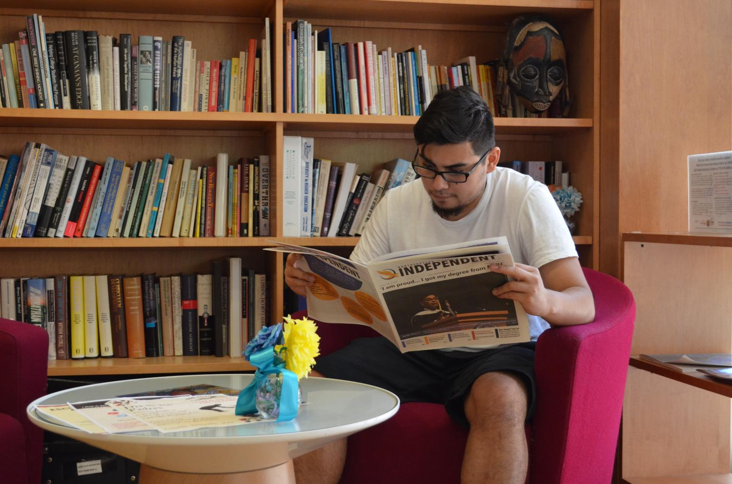 NEIU student Alfredo Palafox reads the Independent next to the Angelina Pedroso for Diversity and Intercultural Affairs Research Center