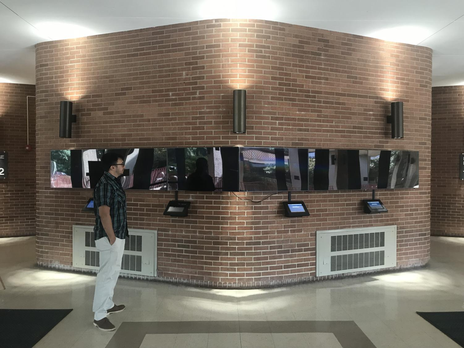 NEIU student Patrick Mercader stares at the pitch-black screens in Lech Walesa Hall. The screens were used to showcase the artwork from NEIU students and faculty protesting Lech Walesa's name after Walesa said homophobic comments.