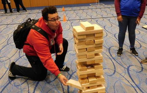 Student participating in the extra-large jenga at Eagle Fest.