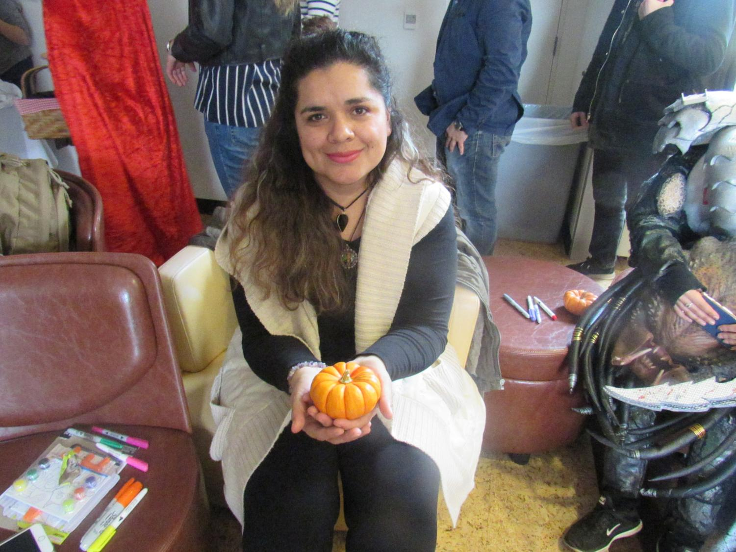 NEIU+student+Daesy+Ruiz+poses+with+mini-pumpkin.