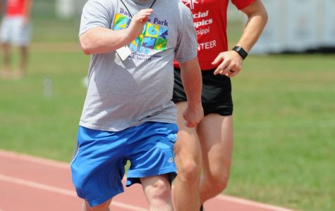 A participant and a volunteer running in a Special Olympics race.
