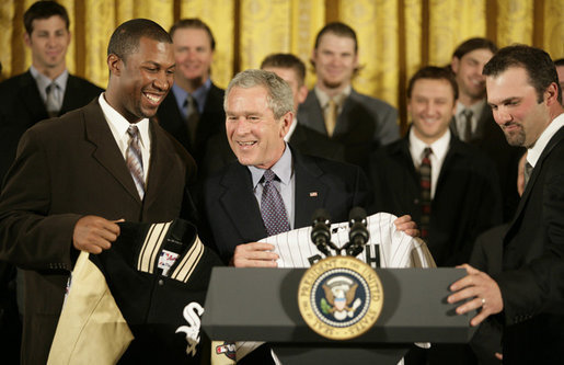 President George W. Bush is presented with a Chicago White Sox jacket and baseball jersey, Monday, Feb. 13, 2006 by White Sox players Jermaine Dye, left, and Paul Konerko in the East Room of the White House, where President Bush honored the 2005 World Series Champions. White House Photo by Eric Draper)