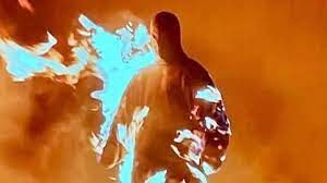 Kanye West walking out of the replica house, on fire.